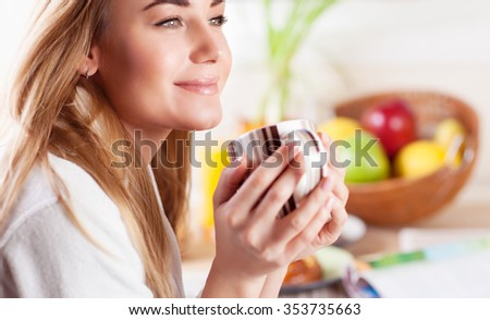 Portrait of cute blond female having coffee in the kitchen, enjoying happy lazy morning, peace and relaxation at home - stock photo