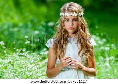 Portrait of cute blond girl dressed in white standing in green field. - stock photo