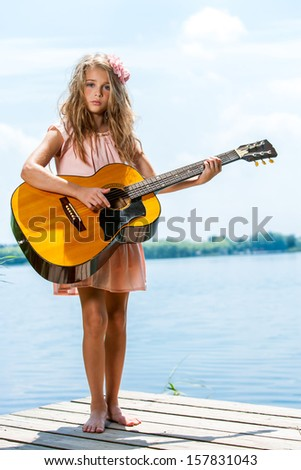 Portrait of cute blond girl standing with guitar at lakeside. - stock photo