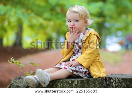 Portrait of cute blonde little child, a toddler girl wearing yellow jacket, sitting on big stump in the park - stock photo