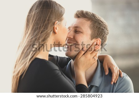 Portrait of cute blonde woman hugging happy boyfriend and kissing in nose - stock photo
