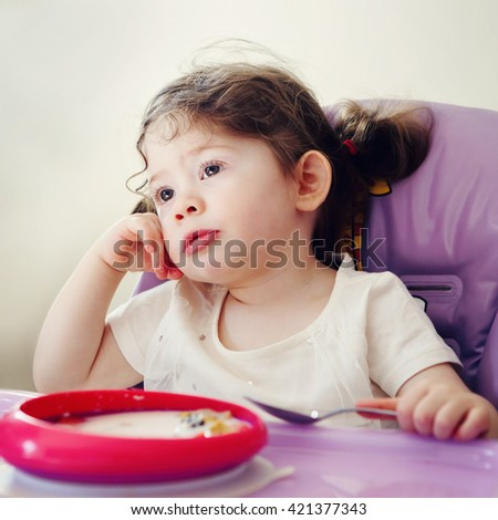 Portrait of cute bored Caucasian child kid girl sitting in high chair eating cereal with spoon early morning, everyday lifestyle candid moments - stock photo