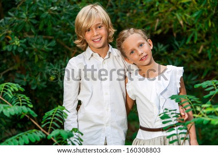 Portrait of cute boy and girl together in green forest. - stock photo