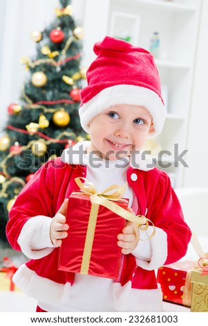 Portrait of cute boy in santa suit with Christmas present  - stock photo