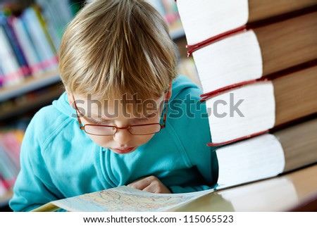 Portrait of cute boy looking at map in library - stock photo