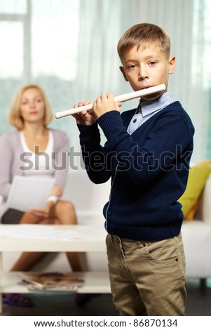 Portrait of cute boy playing the flute with tutor on background - stock photo