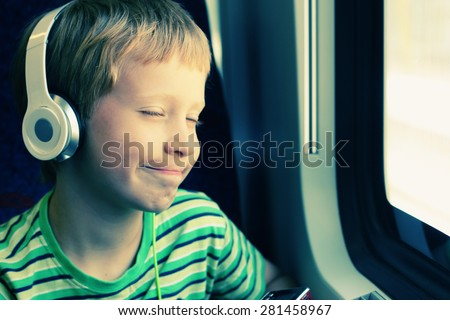 Portrait of cute boy with headphones traveling in the train - stock photo
