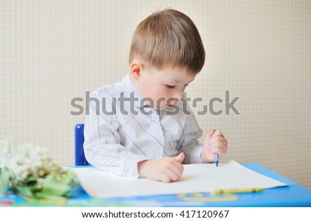 Portrait of cute boy with pen and paper at desk in classroom - stock photo