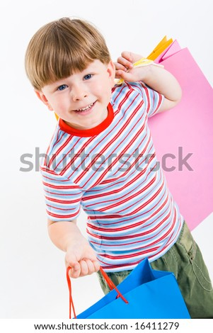 Portrait of cute boy with shopping bags in hands looking at camera isolated over white background - stock photo