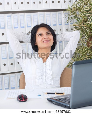 Portrait of cute business woman sitting in office and relaxing with hands behind head - stock photo