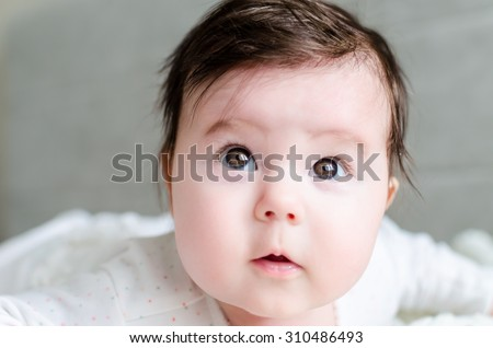 Portrait of cute caucasian newborn baby girl in spotted romper suit looking with beautiful hazel brown eyes and curious glance, lying on woolen blanket on bed at home. The depth of field is short. - stock photo