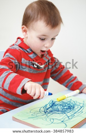 Portrait of cute Caucasian white little boy toddler drawing with color pencils markers on paper in album, looking surprised, excited, mouth open in excitement - stock photo