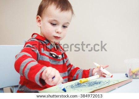 Portrait of cute Caucasian white little boy toddler drawing with color pencils markers on paper in album, looking serious, engaged in process - stock photo