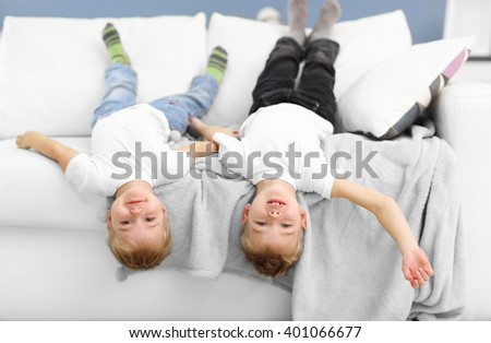 Portrait of cute cheerful brothers playing on sofa in the room - stock photo