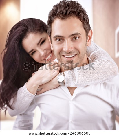 Portrait of cute cheerful family at home, handsome man carry on the back his beautiful wife, happy Valentine day, love concept - stock photo