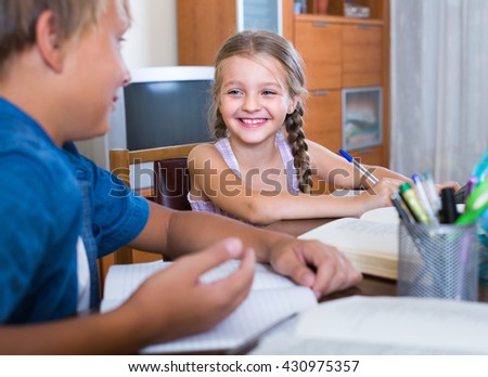 Portrait of cute cheerful little girl and her brother doing homework together - stock photo
