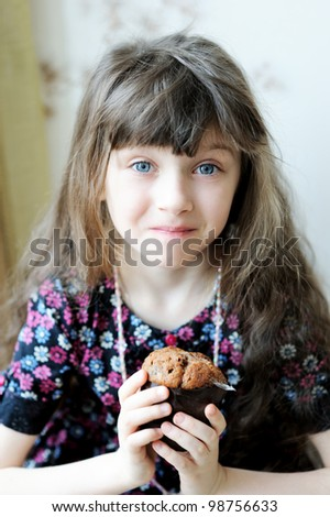 Portrait of cute child girl holding muffin in her hands - stock photo