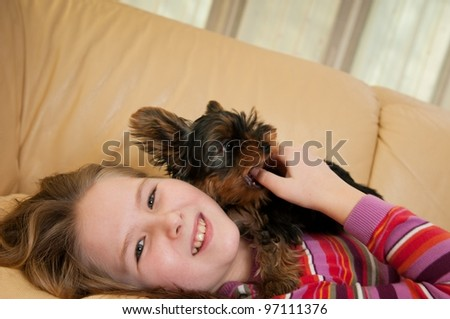 Portrait of cute child (girl) relaxing with little dog - stock photo