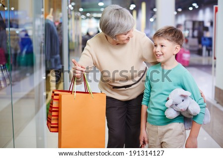 Portrait of cute child looking at shop window with his grandmother holding paperbags near by - stock photo
