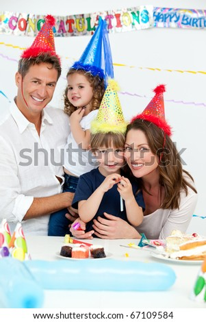 Portrait of cute children with their parents during a birthday party at home - stock photo