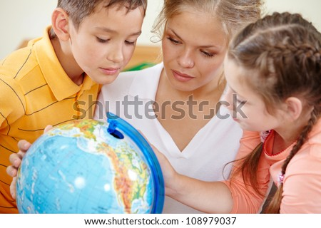 Portrait of cute classmates and teacher looking at globe at geography lesson - stock photo