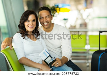portrait of cute couple waiting for flight at airport  - stock photo