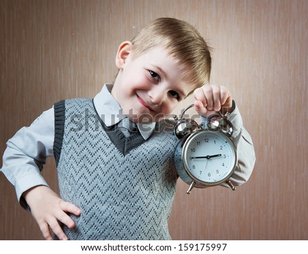 Portrait of cute diligent boy holding alarm clock - stock photo