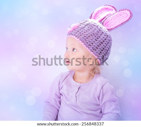 Portrait of cute Easter bunny over blur background, sweet little baby wearing purple hat with rabbit ears, celebrating religious holiday - stock photo