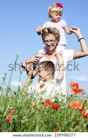 Portrait of cute family in poppy filed during hot summer day - stock photo