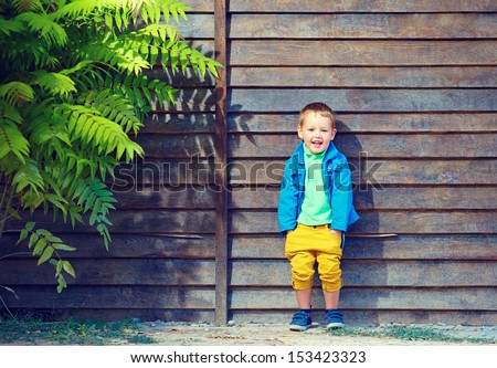 portrait of cute fashionable boy in front of wooden wall - stock photo
