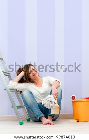 Portrait of cute female painter  sitting on floor after painting. - stock photo