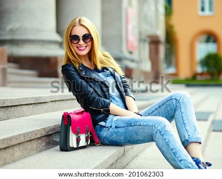 portrait of cute funny modern sexy urban young stylish smiling woman girl model in bright modern cloth outdoors sitting in the park in jeans on a bench in glasses with pink bag - stock photo