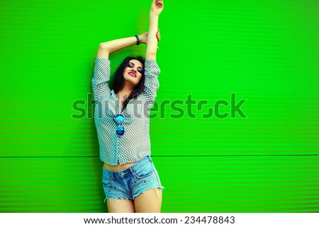 portrait of cute funny sexy young stylish smiling woman girl model in bright modern cloth in jeans shorts with pink lips perfect sunbathed body outdoors in the city near green wall - stock photo