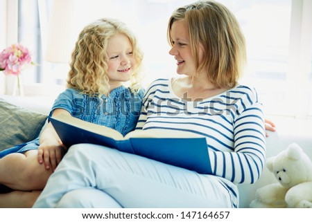 Portrait of cute girl and her mother reading a book at home - stock photo