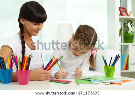 Portrait of cute girl drawing with colorful pencils with her mother near by - stock photo