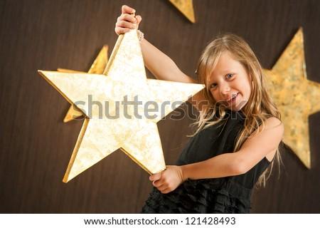 Portrait of cute girl holding big golden star. - stock photo