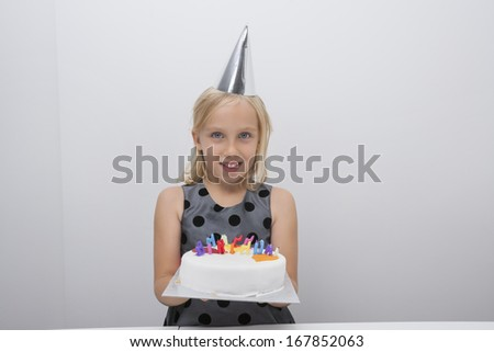 Portrait of cute girl holding birthday cake at home - stock photo