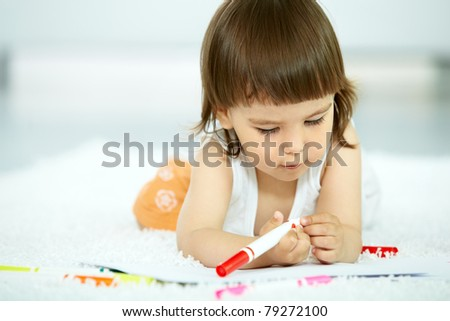 Portrait of cute girl holding highlighter at home - stock photo