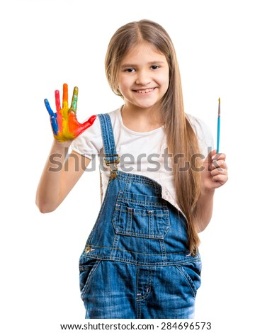 Portrait of cute girl holding paintbrush and showing painted hand - stock photo
