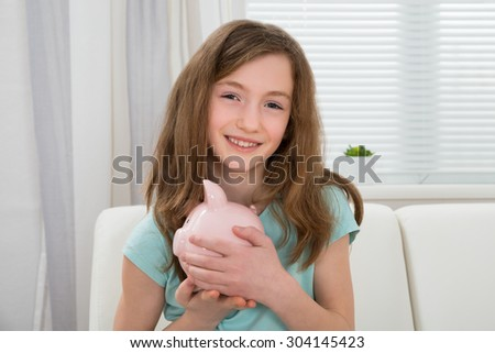 Portrait Of Cute Girl Holding Pink Piggy Bank In Hands - stock photo