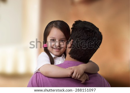 Portrait of cute girl hugging her father - stock photo