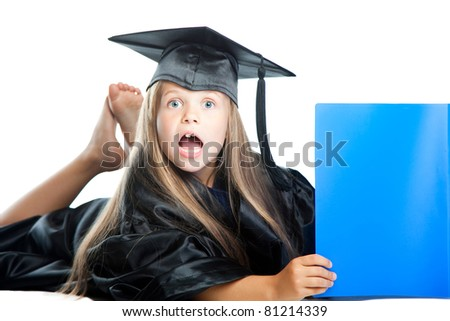 Portrait of cute girl in black academic cap and gown reading big blue book on isolated white - stock photo