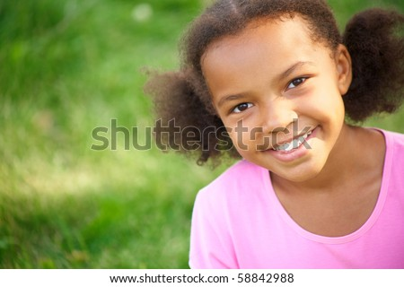 Portrait of cute girl looking at camera and smiling - stock photo