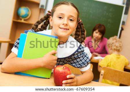 Portrait of cute girl looking at camera during lesson - stock photo