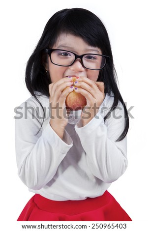 Portrait of cute girl looking at the camera while eating a red apple in the studio, isolated on white - stock photo