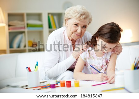 Portrait of cute girl making card for her mom with her grandmother near by - stock photo