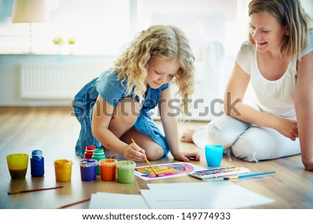 Portrait of cute girl painting with colorful gouache with her mother near by - stock photo