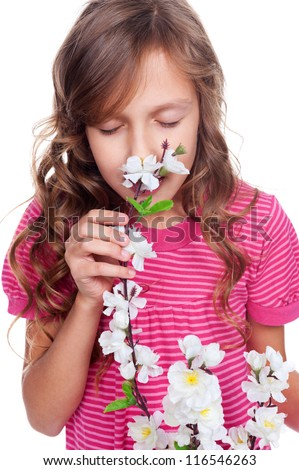 portrait of cute girl smelling spring flowers over white background - stock photo