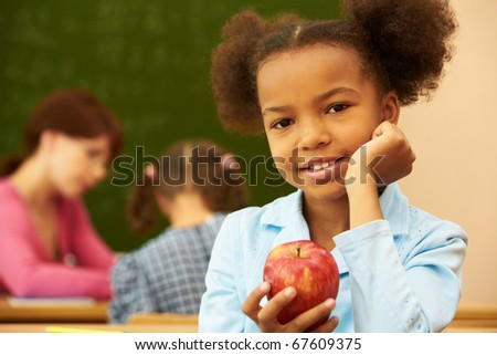 Portrait of cute girl with apple looking at camera during lesson - stock photo