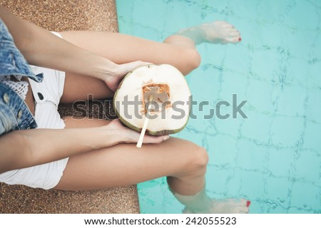 portrait of cute girl with coconut cocktail in the tropical pool. Horizontal. Outdoors lifestyle - stock photo